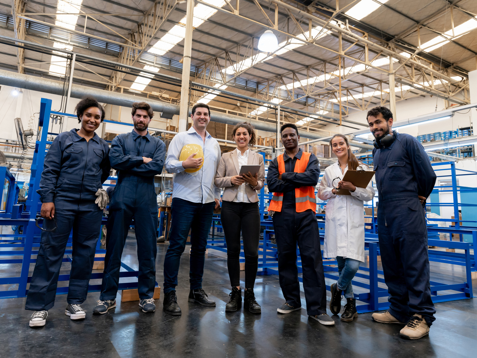 Diverse large group of employees at a manufacturing water pump factory all smiling at camera - Full body length